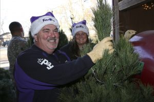 FedEx employees and military members with Christmas Trees